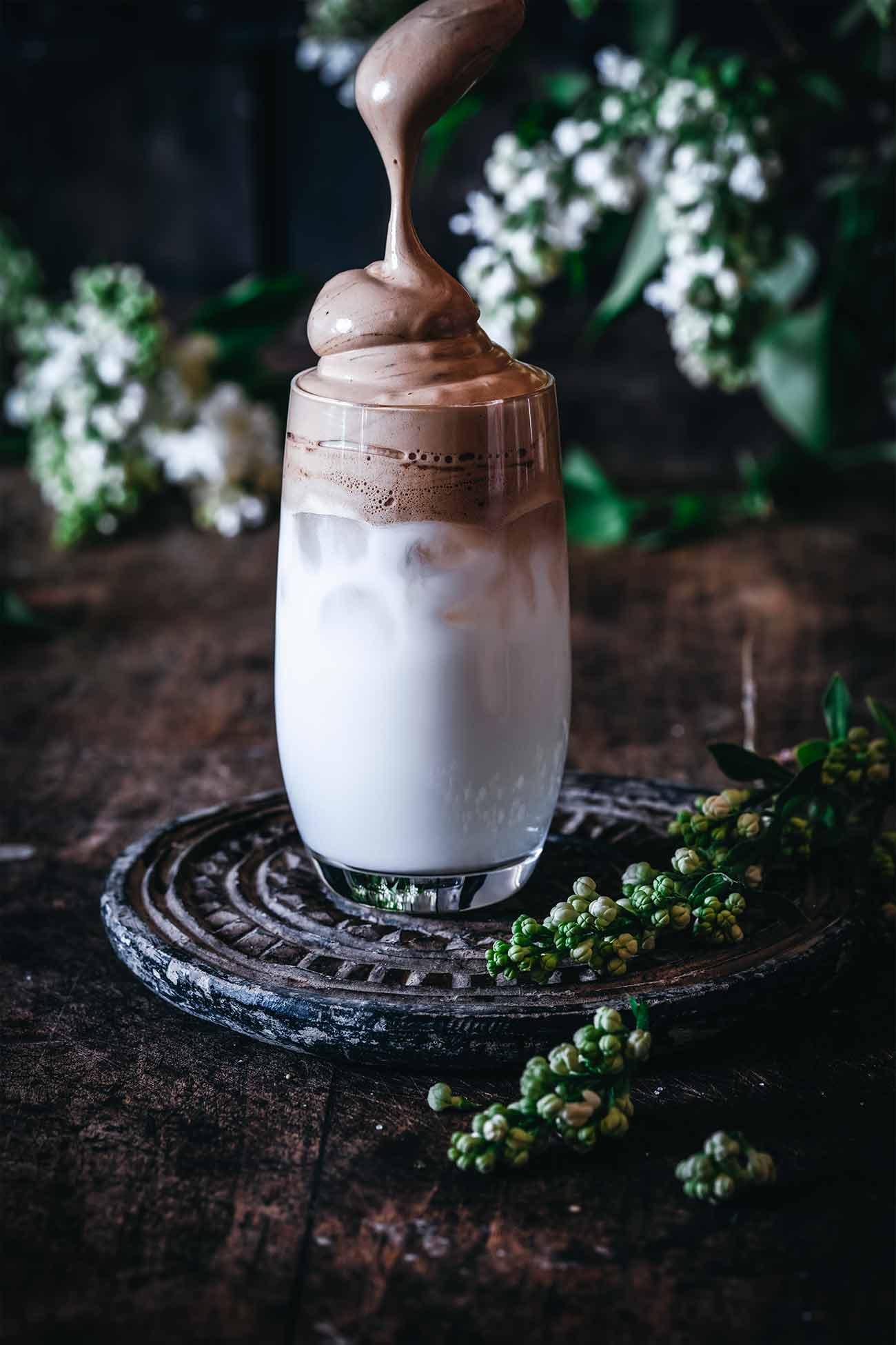 Die Variationen sind zahlreich. Klassisch als Kaltgetränk verrührt man 1 TL löslichen Kaffee (oder 1 Stick Jacobs Löskaffee) mit 1 TL Zucker und 1 TL heißen Wasser zu einer dickflüssigen Masse. Ich mache das in der Küchenmaschine, denn da geht es richtig schnell und die Masse wird schön fest. Dann kommen einige Eiswürfel ins Glas, kalte Milch und obendrauf die köstliche Kaffeecreme.  Funktioniert natürlich auch mit heißer Milch und ohne Eiswürfel.