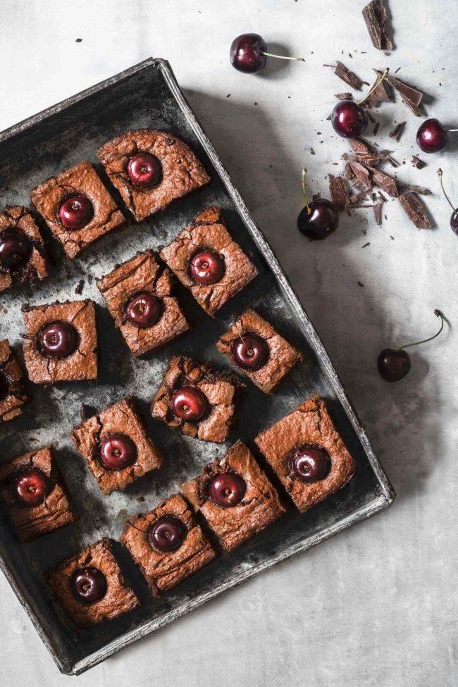 """Cherry-Chocolate Cake Kirsch-Schokoladen Kuchen Es gibt Kuchen und es gibt """"DIE"""" Kuchen. DIE Kuchen sind voller Schokolade und innen noch ganz saftig. Ich kann dann kaum erwarten diese in Stücke zu schneiden und Menschen (also die, die ich kenne) in den Mund zu stecken. Denn ich weiß ganz genau was passiert: noch während sie kauen, verdrehen sie leicht die Augen und ein """"WOW"""" ertönt. Ich mag das. Natürlich kannst du auch Kirschen ohne Kerne nehmen, aber für das Foto sahen die Kirschen mit Stil einfach schöner aus. 1 Form ca. 20 x 20 cm 100 g Butter 400 g Vollmilchschokolade 4 Eier 150 g Zucker 1 Prise Salz 200 g gemahlene Mandeln 2 EL Kirschwasser 6 EL Mehl ca. 20 Kirschen Butter und Schokolade über einem Wasserbad langsam schmelzen lassen Eier mit Zucker und Salz schaumig aufschlagen Schokoladenmasse, Mandeln, Kirschwasser und Mehl zugeben und verrühren Backofen auf 200 Grad Ober-Unterhitze vorheizen und eien Springform mit Backpapier auslegen Teig in die Form geben und glatt streichen Die Kirschen in den Teig drücken Teig im Ofen 25 -30 Minuten backen (falls der Kuchen zu dunkel wird, mit Alufolie abdecken), herausnehmen und vollständig abkühlen lassen"""