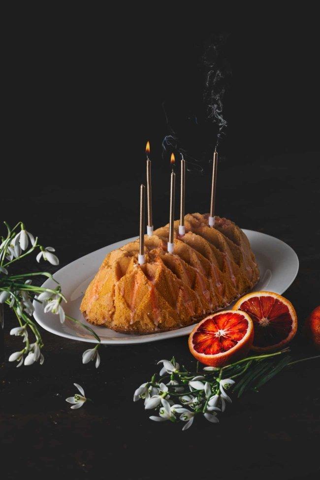 Ich musste noch einmal bei den Blutorangen zuschlagen, bis die Saison dann bald vollständig vorbei ist. Der griechische Joghurt im Kuchen, in Kombination mit der Blutorange, lässt ihn fast wie ein Softeis schmecken. Ich habe noch ein paar Kerzen auf den Kuchen gepackt. Sah irgendwie besser aus. Zu feiern gibt es ja eh ständig etwas.