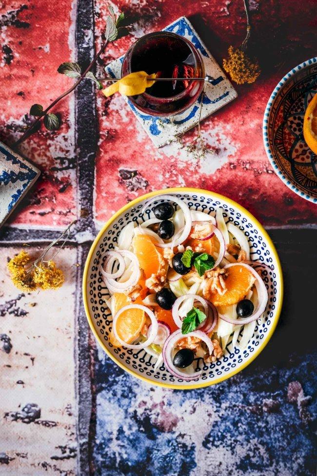 Insalata di arance siciliana 4 Portionen 2 Fenchelknollen 2 Orangen 1 rote Zwiebel, geschält und in Scheiben geschnitten 8 Walnüsse, grob gehackt 1 Handvoll schwarze Oliven, entsteint 1 cm frischen Ingwer, fein gehackt 2 Stiele frische Minze Salz Olivenöl extra vergine Rotweinessig Äußere Blätter und Stängel vom Fenchel entfernen und Fenchel in feine Spalten schneiden oder fein hobeln Den Saft einer Orange auspressen und auffangen, zweite Orange filetieren. Fenchel, Orangenspalten zusammen mit Ingwer und Walnüssen vermengen. Oliven und Zwiebeln untermengen. Mit Salz, Olivenöl, Orangensaft und etwas Essig vermengen und mit frischer Minze servieren