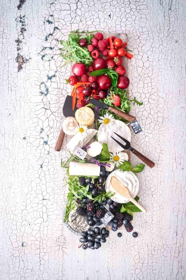 """Bei mir landen sie alle auf dem Tisch: Jede Art von Ziegenkäse. Als Käse-Fan ist es doch ganz klar, dass ich fast alle Käsesorten liebe. Besonders Ziegenkäse hat es mir angetan, da er so vielfältig einsetzbar ist. Aber aus Frankreich muss er sein. Warum? Der schmeckt mir einfach am besten. Ich kann mich noch ganz genau daran erinnern, als ich das erste Mal den Südosten Frankreichs (Rhône-Alpes) bereist habe und eines Abends in einem Bauernhof-Restaurant zum Essen einkehrte. Ich bestelle eine Käseplatte, frisches Brot und ein Glas Wein. Bis dato wusste ich nicht einmal das Frankreich so ein bekanntes Ziegenkäse-Gebiet hat. Man klärte mich schnell auf, denn gerade das milde Klima und die Berglandschaft der Pyrenäen gebe dem Heu den besonderen Charakter und somit der Ziegenmilch den besonderen Geschmack. Und das schmeckt man auch. Ganz im """"Frankreich-Fieber"""" habe ich meine Käseplatte der französischen Flagge angeglichen. Der Selles-Sur-Cher AOP mit seiner gräulichen Färbung der Rinde (die durch das Bestäuben mit Pflanzenkohle entsteht) durfte farblich noch mit in den blauen Teil. Die anderen Käsesorten erstrahlen im hellen weiß, so dass sie das Mittelstück (und damit das Herzstück) der Käseplatte ausmachen."""