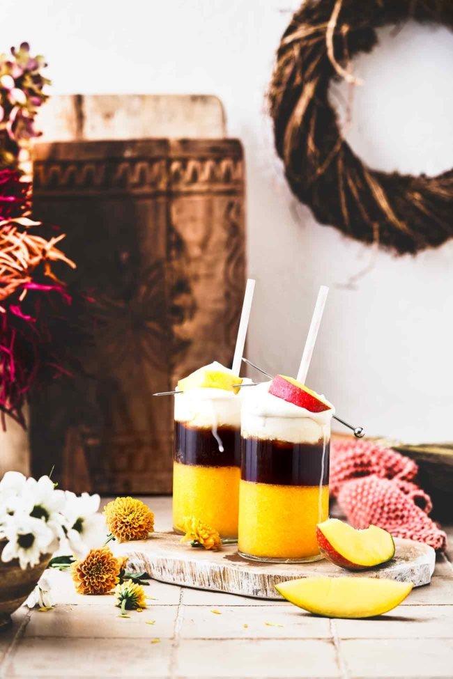 """Mango und Kaffee passen einfach perfekt zusammen. Frische, pürierte Mango aufgegossen mit einem Cold Brew und als Topping ein Klecks Sahne, das hört sich doch nach einer perfekten Erfrischung an, bevor uns der Herbst einholt, oder? Die Kaffeebohnen der Jacobs Expertenröstung Crema Italiano eignen sich perfekt für den """"coolen"""" Drink, denn die dunkle Röstung harmonisiert richtig gut mit der aromatischen, süßen Mango."""