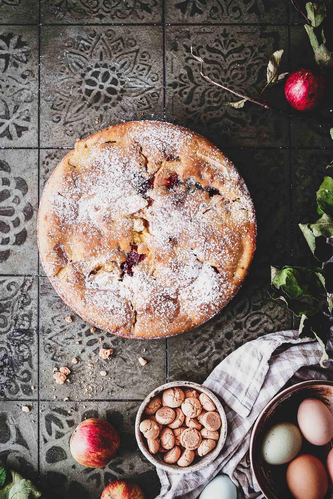 Apfelkuchen. Ich mag sie einfach alle. Aber dieser ist etwas ganz Besonderes, denn der hat nicht fruchtige Äpfel, sondern auch ein paar knackige Amarettinis in sich. Na ja… und etwas Weißwein und ein paar Kleckse Kirschmarmelade sind auch noch dabei. Ein gelungener Kuchen mit Crunch-Effekt.