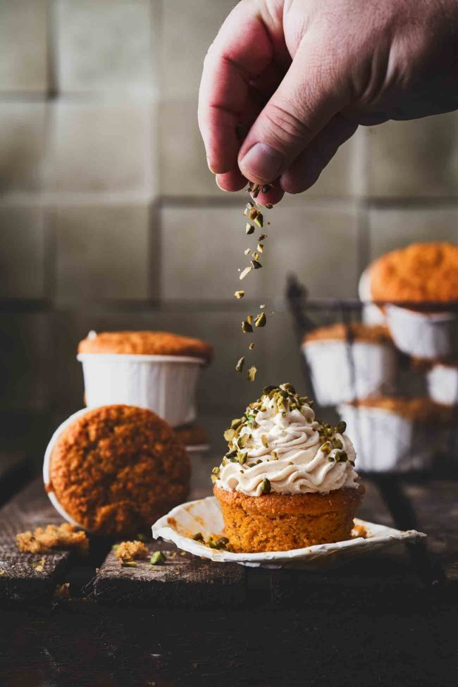 """Ihr liebt Karottenkuchen auch, weil er so schön saftig ist, oder? Warum nicht """"Carrot Cake"""" Muffins daraus machen? Als Topping bekommen sie eine Haube aus einer Frischkäse-Buttercreme mit etwas Sesammus. Die Kombination aus Karotte, Walnüssen und Sesam ist einfach unglaublich lecker."""
